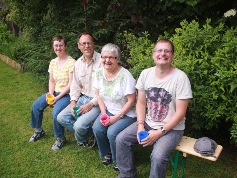 Vier Bewohne sitzen im Garten des Birkenhofs.