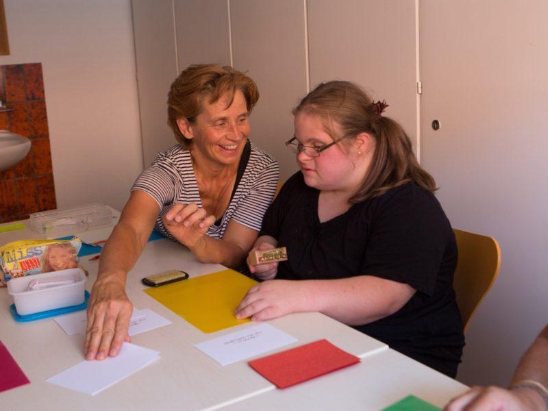 Ein Angestellte und eine Bewohnerin stellen gemeinsam Karten her