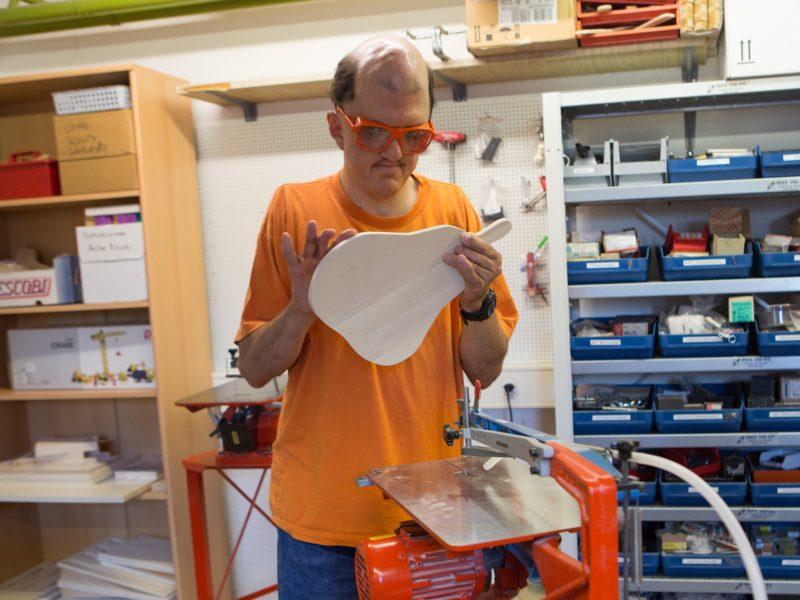 Ein Bewohner begutachtet ein Brett aus Holz, das er gerade ausgesägt hat