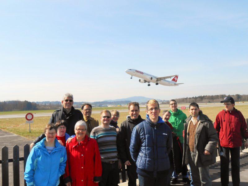 Die Bewohner vor der Landebahn des Flughafen Zürich mit einem Flugzeug im Hintergrund