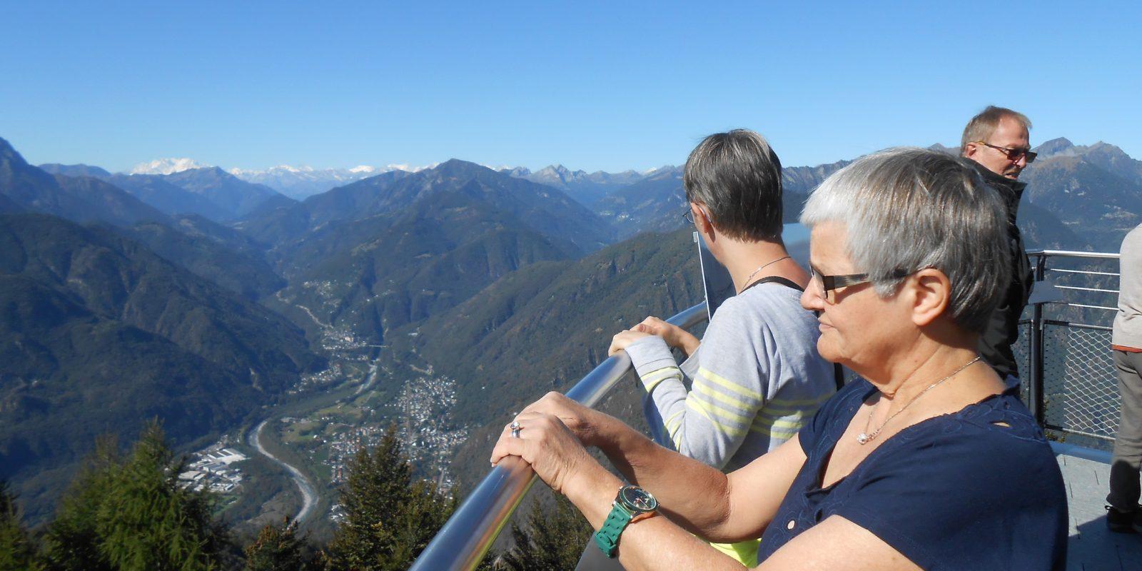 Zwei Bewohnerinnen stehen auf einer Aussichtsplattform und schauen über die Berge